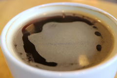 Close up of hot black coffee in a white cup with thin layer of form, selective focus. Background Stock Photo