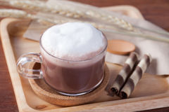Close up hot chocolate milk with snack on wooden plate on wooden Royalty Free Stock Image