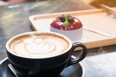 Close up hot coffee with latte art and cake with garden backyard. In background, Lifestyle concept royalty free stock photography
