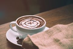 Close up of Hot coffee latte art with pattern on top. Warm feeling coffee, vintage cup with coffee bean burlap Stock Photo