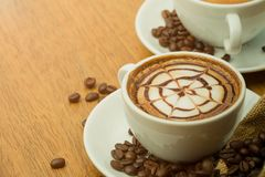 Close up of Hot coffee latte art with pattern on top. Warm feeling coffee, vintage cup with light flare Stock Photos
