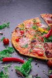 A close-up of hot margarita pizza on a dark background. Cut Italian pizza with vegetables and meat. Copy space. stock photo