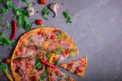 A close-up of hot margarita pizza on a dark background. Cut Italian pizza with vegetables and meat. Copy space. royalty free stock photo