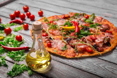 A close-up of hot margarita pizza on a rustic table background. Whole Italian pizza with vegetables and olive oil. royalty free stock photography