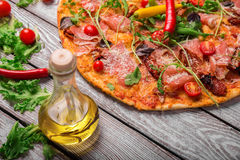 A close-up of hot margarita pizza on a rustic table background. Whole Italian pizza with vegetables and olive oil. royalty free stock image