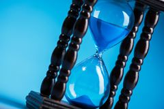 Close up of hourglass. On a blue background Stock Photos