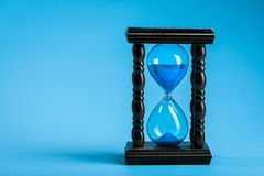 Close up of hourglass. On a blue background Royalty Free Stock Photos