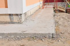Close up on house foundation waterproofing, damp proofing with concrete path to avoid water leaks for house wall. Close up on home foundation waterproofing royalty free stock photos