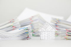 Close up house have blur pile overload paperwork as background. Close up house have blur pile overload paperwork of report and receipt with colorful paperclip Royalty Free Stock Photo
