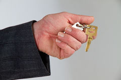 Close-up of house keys held by house agent. Focus on hand with key Stock Image