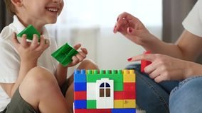 Close-up of the house from meccano. A woman and a little boy build a house of colored blocks, experiencing emotions of. Happiness and laughter. Slow motion stock footage