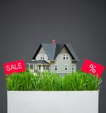 Close up of house model with grass and sale tablet Royalty Free Stock Image