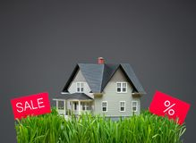 Close up of house model with grass and sale tablets Royalty Free Stock Image