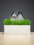 Close up of house model with green grass on stand. Close up of house model with green grass on grey background. Concept of real estate and building Stock Images