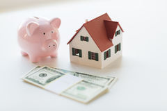 Close up of house model, piggy bank and money Royalty Free Stock Photo