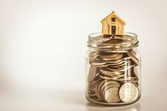 Close up house model place on stacking of money coin for a home mortgage and loan ,  refinance or property investment concept. Close up house model place on stock photo