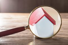 House Model Seen Through Magnifying Glass. Close-up Of A House Model Seen Through Magnifying Glass On Wooden Table royalty free stock photos