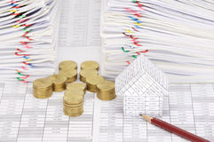 Close up house and pencil with coins have dual document. Close up house and pencil with step pile of gold coins on finance account have dual pile overload Royalty Free Stock Images