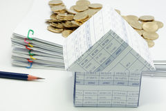 Close up house with pencil and pile of gold coins. And pile overload document with colorful paperclip have blur on white background royalty free stock images