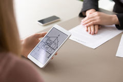 Close up of house plan on tablet, real estate contract. Close up view of architectural house plan on tablet screen and rental lease or sale purchase contract on Royalty Free Stock Image