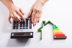 Close-up Of A House Showing Energy Efficiency Rate. In Front Of Businesswoman Using Calculator stock images