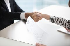 Close up of HR manager handshaking male applicant at interview royalty free stock images