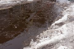 Close-up of huge puddles of snow on city streets. The shadow of stock photo