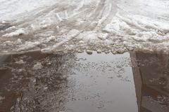 Close-up of huge puddles of snow on city streets. The shadow of royalty free stock photo