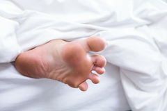 Close-up of human foot on bed Royalty Free Stock Photography