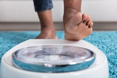 Human Foot Stepping On Weighing Scale. Close-up Of A Human Foot Stepping On Weighing Scale royalty free stock photos