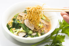 Close up of human hand grabbing noodles with chopsticks from a b Royalty Free Stock Images