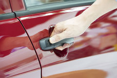 Close up of human hand opening door of car. Royalty Free Stock Image