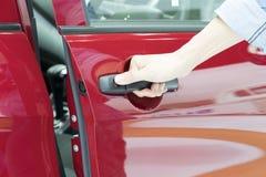 Close up of human hand opening door of car. Royalty Free Stock Photos
