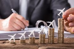Human Hand Placing Small Aeroplane On Increasing Stacked Coins. Close-up Of A Human Hand Placing Small Aeroplane On Increasing Stacked Coins Over Wooden Desk stock photo