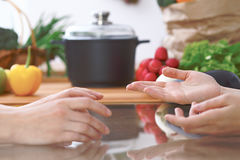 Close-up of human hands are gesticulate over a table in the kitchen. Women choosing menu or making online shopping. So Royalty Free Stock Images