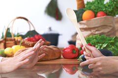 Close-up of human hands are gesticulate over a table in the kitchen. Women choosing menu or making online shopping. So Stock Image