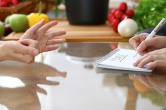 Close-up of human hands are gesticulate over a table in the kitchen. Women choosing menu or making online shopping. So Stock Photos