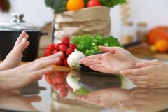Close-up of human hands are gesticulate over a table in the kitchen. Women choosing menu or making online shopping. So Royalty Free Stock Photos