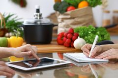 Close-up of  human hands are gesticulate over a tablet in the kitchen. Friends having fun while choosing menu or makin Royalty Free Stock Photo