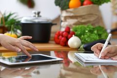 Close-up of  human hands are gesticulate over a tablet in the kitchen. Friends having fun while choosing menu or makin Royalty Free Stock Photos