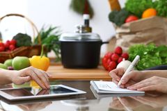 Close-up of  human hands are gesticulate over a tablet in the kitchen. Friends having fun while choosing menu or makin Stock Images