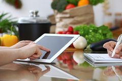 Close-up of  human hands are gesticulate over a tablet in the kitchen. Friends having fun while choosing menu or makin Royalty Free Stock Images