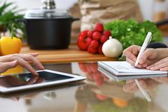 Close-up of  human hands are gesticulate over a tablet in the kitchen. Friends having fun while choosing menu or makin Stock Photography