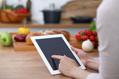 Close-up of human hands are gesticulate over a tablet in the kitchen. Women choosing menu or making online shopping. So Stock Image