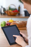 Close-up of human hands are gesticulate over a tablet in the kitchen. Women choosing menu or making online shopping. So Royalty Free Stock Photo