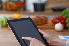 Close-up of human hands are gesticulate over a tablet in the kitchen. Women choosing menu or making online shopping. So Royalty Free Stock Photography
