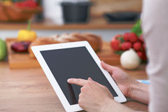 Close-up of human hands are gesticulate over a tablet in the kitchen. Women choosing menu or making online shopping. So Royalty Free Stock Image
