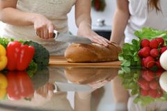 Close-up of human hands slicing bread in a kitchen. Friends having fun while cooking in the kitchen. Chef cook represent Stock Photo