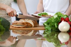 Close-up of human hands slicing bread in a kitchen. Friends having fun while cooking in the kitchen. Chef cook represent Stock Images