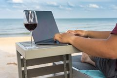 Close up of human hands typing laptop on beautiful beach. Human hands typing laptop with glass of wine on beach stock photography